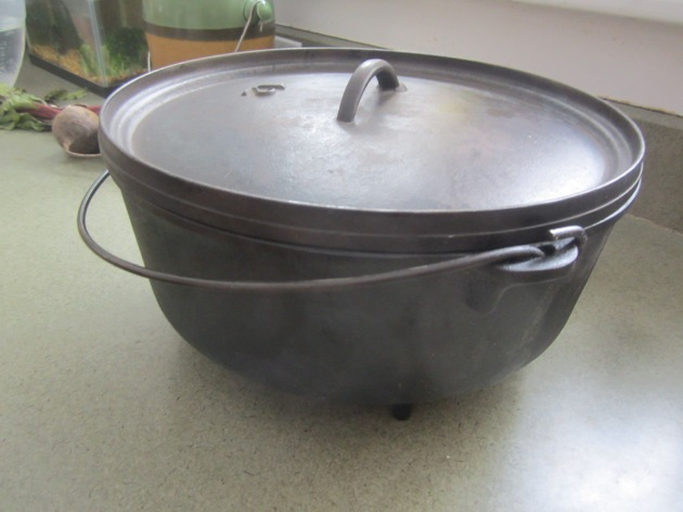 Three-legged cast iron dutch oven with a lid that has a slight inversion, perfect for hearth cooking.