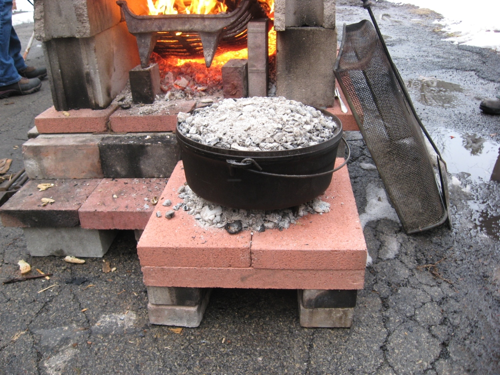 Coals above and below the dutch oven.