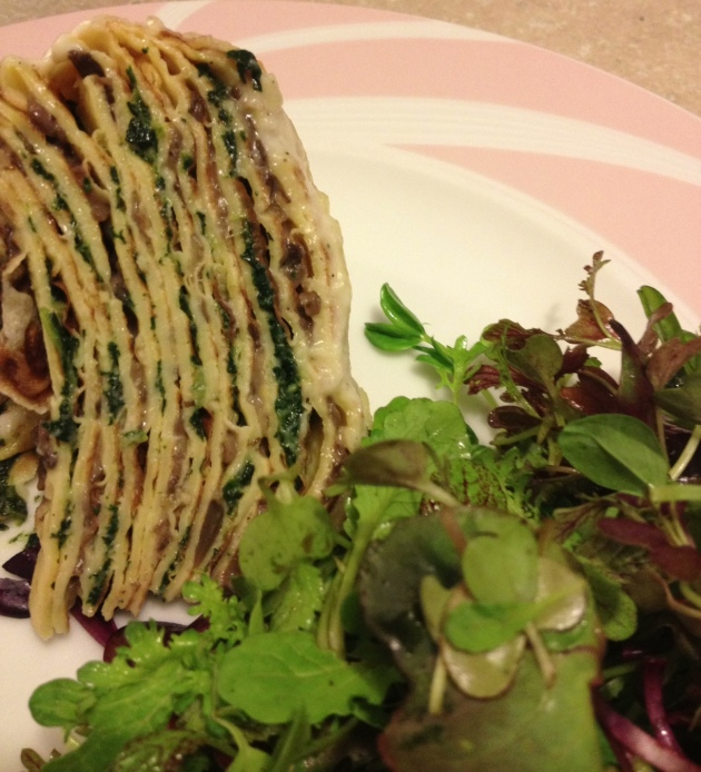 A side view of the crepe stack, with a micro green salad.